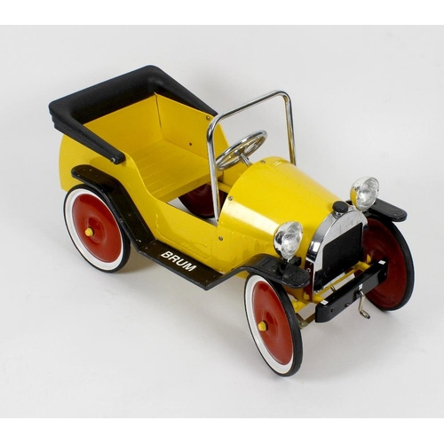 593 - A modern pressed metal child's pedal car, the yellow painted body with tubular metal window frame an...