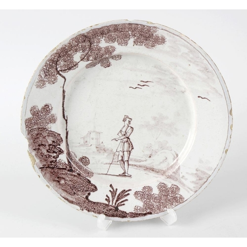 67 - An 18th century English Delftware plate, possibly Wincanton, decorated in manganese with a figure in...