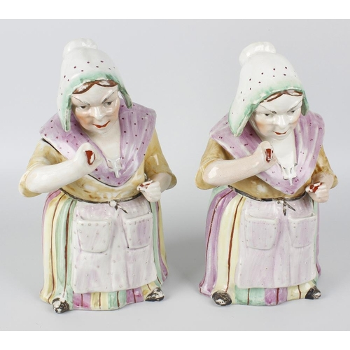 71 - Two unusual 19th century Staffordshire() pottery tobacco jars and covers, each modelled as a lady dr...