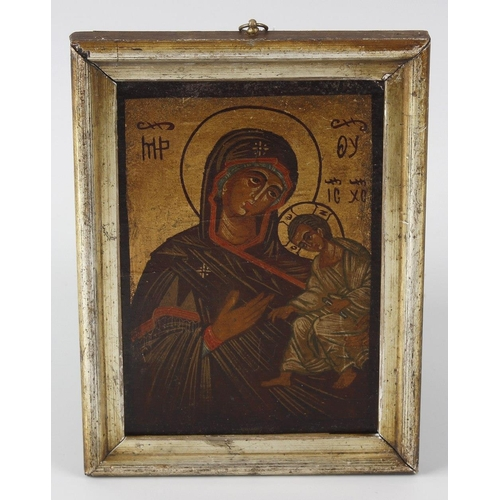 712 - A hand painted and gilded orthodox wooden ikon panel depicting The Madonna and Child, 7 (18cm) x 4,7...