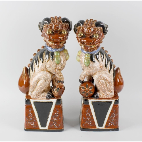 78 - A pair of 20th century Oriental porcelain Dogs of Fo, male and female, each modelled in seated pose ...