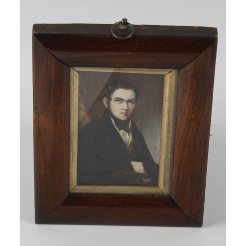 793 - A 19th century painted portrait upon ivory panel, half length study of a young gentleman seated in a...