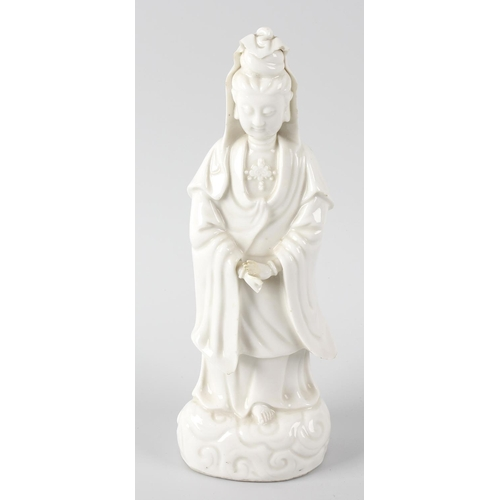 80 - A 19th century Chinese blanc de chine figure, modelled as Guanyin stood in flowing robes upon a wave...