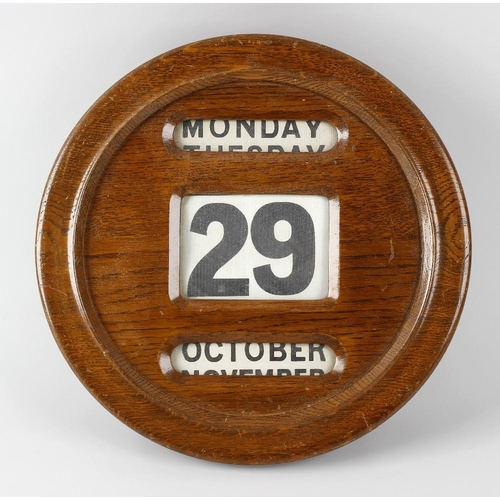 801 - An early 20th century oak wall calendar, of circular form with three windows displaying day, date an...