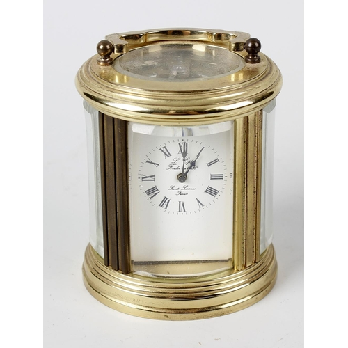 838 - A 20th century oval mignonette carriage clock, L'Epee, Sainte-Suzanne, having a white Roman dial, th...