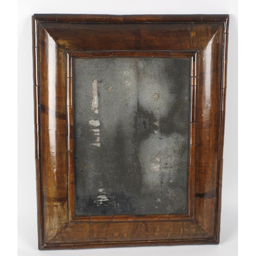 851 - A Queen Anne wall mirror, of rectangular form, the glass with curved and bevelled edged walnut surro...