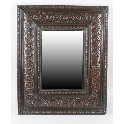 853 - An oak framed wall mirror, the bevelled edged mirror of rectangular form, with conforming carved rec...