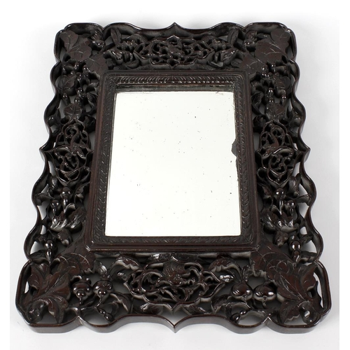 854 - A Chinese zitan wood wall mirror, the pierced and carved frame detailed with heads of birds amidst l...