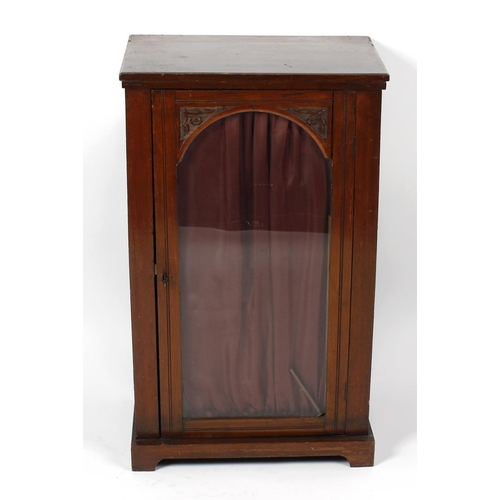 860 - A late 19th century carved oak music cabinet, the rectangular top over arch-glazed door with stipple...
