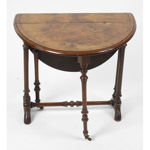 875 - A small mid Victorian walnut Sutherland table. The top and oval flaps with figured border and ebony ...