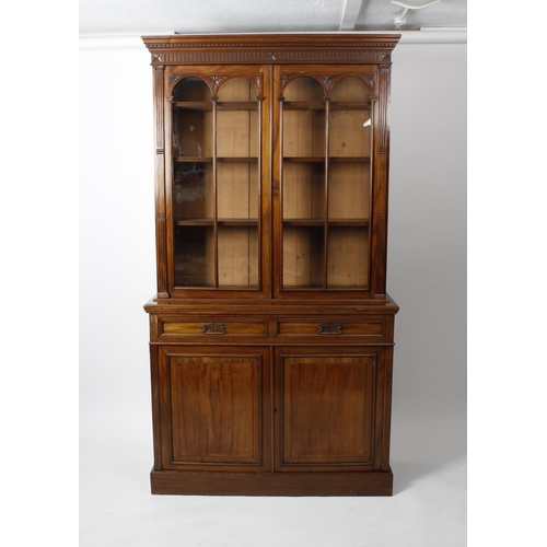 878 - A late Victorian carved mahogany bookcase cabinet. The upper stage having a moulded dentil cornice a...