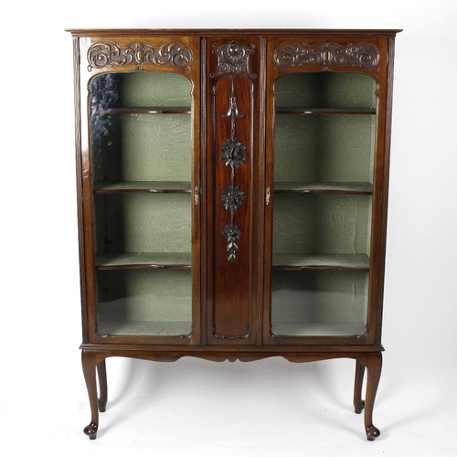880 - An Edwardian mahogany display cabinet or vitrine. The moulded cornice over a pair of shaped arch-gla...