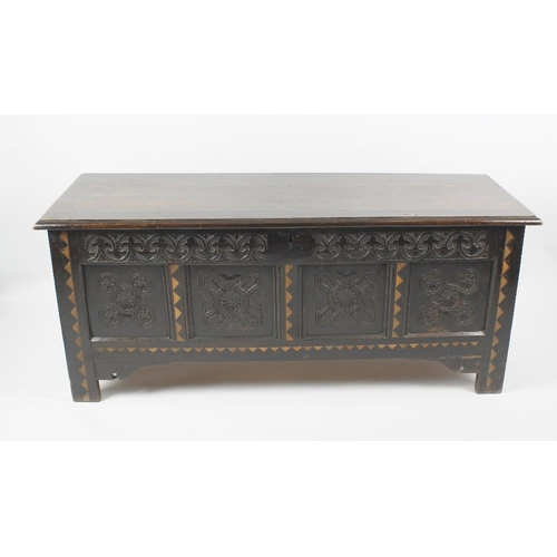 881 - A 17th century and later inlaid oak coffer, the later four-plank hinged lid with moulded edge, the p...