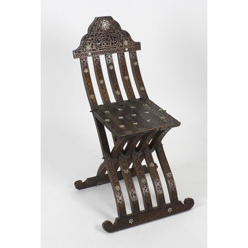 884 - A Middle Eastern carved and inlaid folding occasional chair. The mother-of-pearl star-inlaid shaped ...