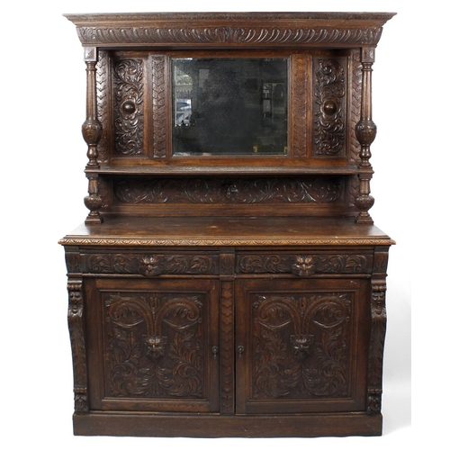 892 - A late 19th century carved oak mirror-back sideboard, the upper stage having a foliage-carved cornic...