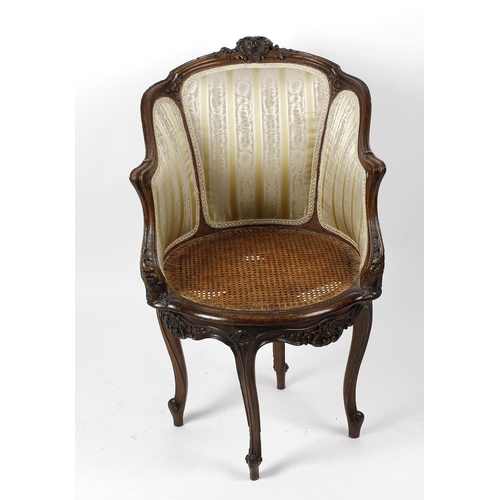 908 - A late 19th century French oak revolving tub salon chair, in Louis XV style with foliate scroll cres...
