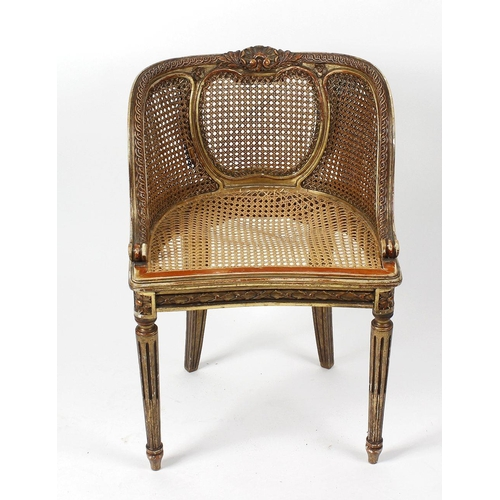 909 - A small late 19th century French giltwood double-cane bergere tub salon chair, in the Louis XVI tast...