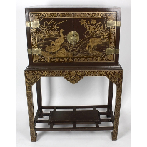 915 - A Chinese brown lacquer cabinet on stand. The rectangular top and twin doors finely decorated with b...