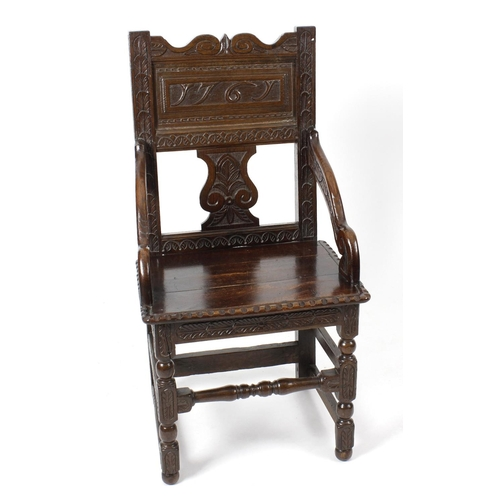 921 - An unusual carved oak elbow chair of wainscot type, mid 18th century and later, the back with oppose...