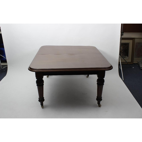 925 - A Victorian mahogany wind-out extending dining table. The moulded oblong top extending with two addi...