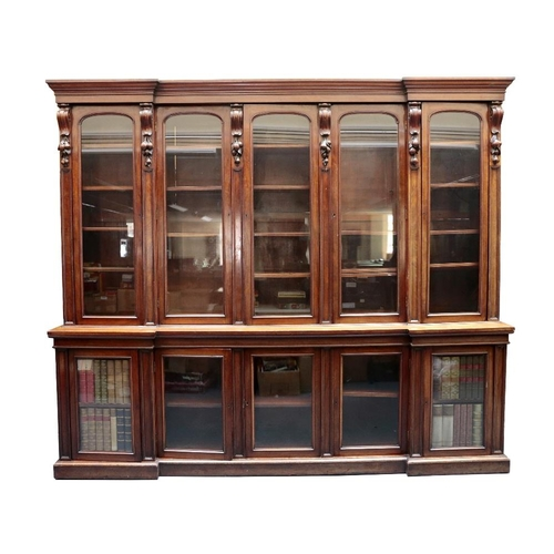 929 - An imposing Victorian mahogany library bookcase. Of five-section inverted breakfront design, the upp...