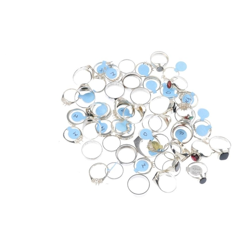 1028 - A bag containing fifty-eight dress rings and ring mounts. In a variety of designs, to include a bloo...