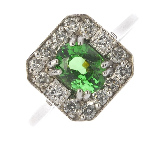 107 - A garnet and diamond cluster ring. Of square outline, the oval-shape green garnet, with brilliant-cu...