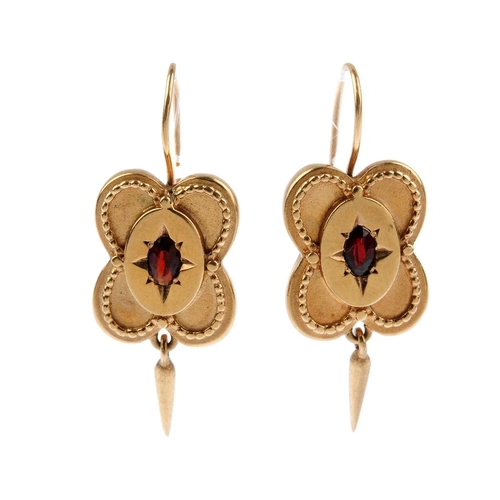 109 - A pair of garnet earrings. Each designed as an oval-shape garnet, inset to a stylised star setting, ...