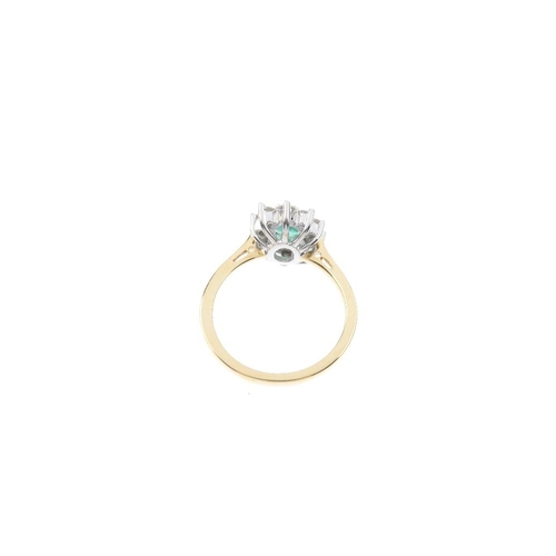 111 - An 18ct gold emerald and diamond cluster ring. The oval-shape emerald, within a brilliant-cut diamon...