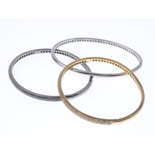 1118 - (131747-1-C) Three 18ct gold diamond, coloured diamond and gem-set bangles. The first designed as a ...