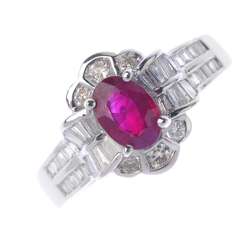 112 - An 18ct gold ruby and diamond cluster ring. The oval-shape ruby, within a brilliant and tapered bagu...