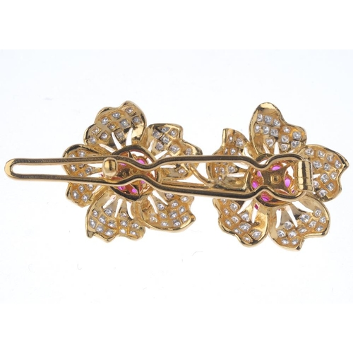 1123 - (131747-1-H) A ruby and diamond floral hair clip. Comprising two circular-shape ruby clusters, each ...