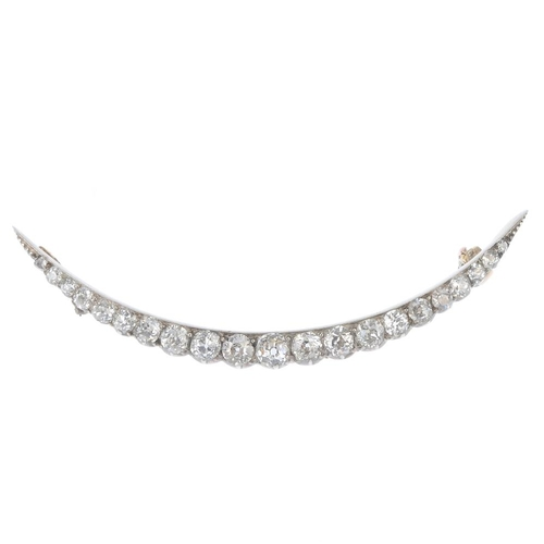 113 - A late Victorian silver and gold diamond crescent brooch, circa 1880. Set with graduated old-cut dia...