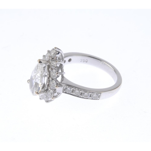 1135 - (131919-2-A) An 18ct gold diamond dress ring. The pear-shape diamond, with brilliant-cut diamond sur...