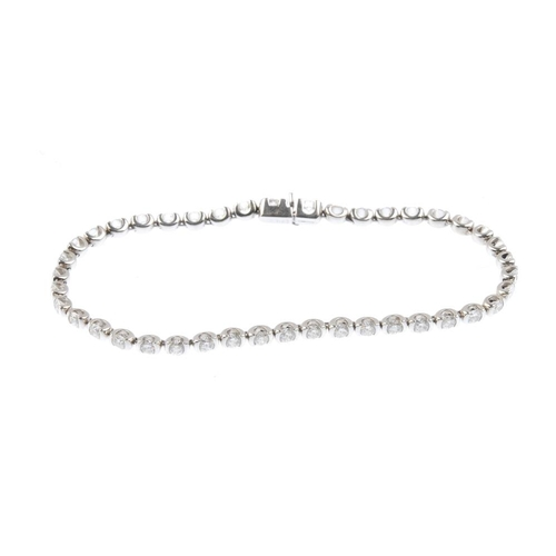 1162 - (3694-12-A) THEO FENNELL - an 18ct gold diamond bracelet. The brilliant-cut diamond line, with push-...