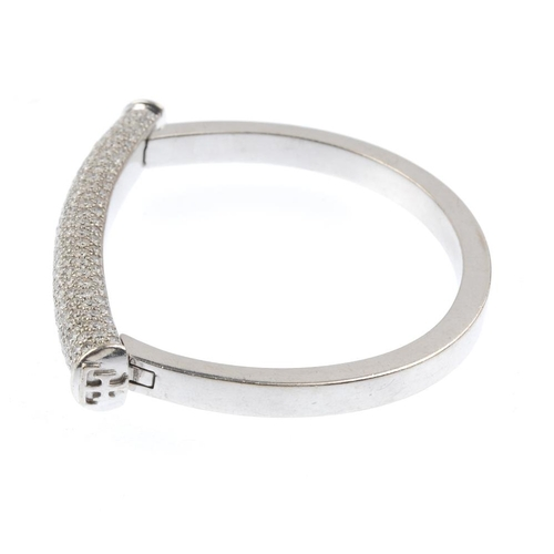 1168 - (3694-6-A) THEO FENNELL - an 18ct gold diamond 'shaft' bangle. The pave-set diamond bar, with Theo F...