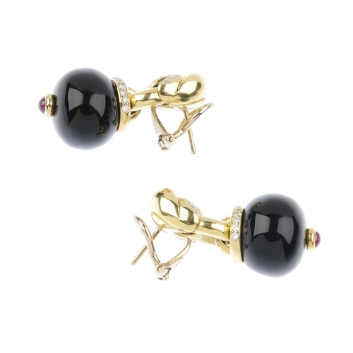 1173 - (3752-2-A) A pair of gem-set earrings. Each designed as an onyx bead, with circular ruby cabochon ac...