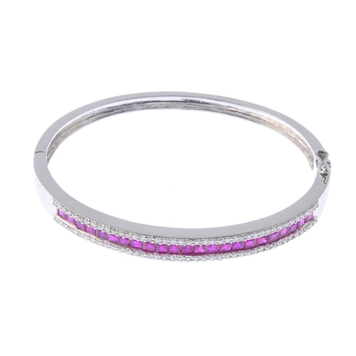 1183 - (4073-3-A) A ruby and diamond hinged bangle. The square-shape ruby line, with brilliant-cut diamond ...
