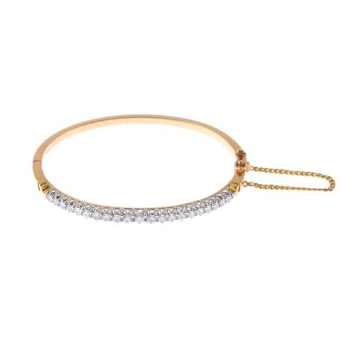 1184 - (4073-4-A) A diamond bangle. The graduated brilliant-cut diamond line, with plain half-bangle. Estim...