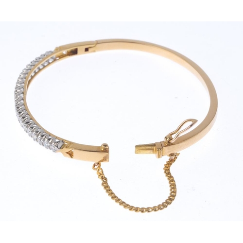 1184 - (4073-4-A) A diamond bangle. The graduated brilliant-cut diamond line, with plain half-bangle. Estim...