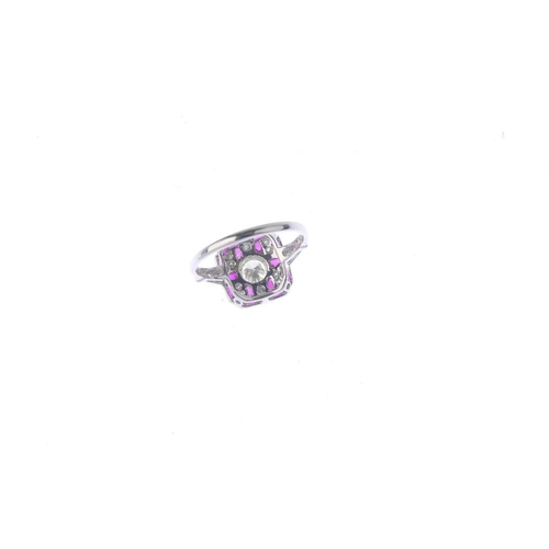 121 - A ruby and diamond dress ring. Of geometric design, the brilliant-cut diamond collet, with calibre-c...