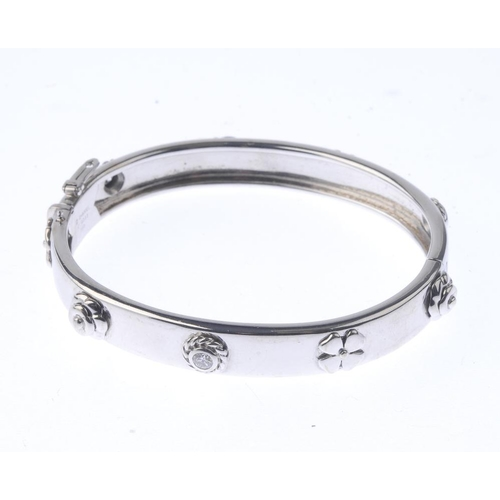 1228 - (401729-1-A) CHANEL - a diamond hinged bangle. With brilliant-cut diamond collet and flower detail. ...