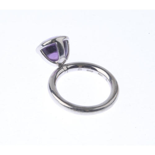 1242 - (401784-1-A) GARRARD - an 18ct gold amethyst single-stone ring. The circular amethyst cabochon, arti...