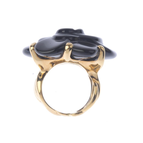 1245 - (401791-1-A) CHANEL - A floral ring. The carved black-gem flower, with foliate band. Signed Chanel. ...