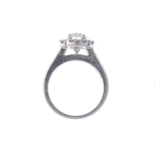 1262 - (546800-1-A) A diamond cluster ring. The brilliant-cut diamond, with a similarly-cut diamond surroun...