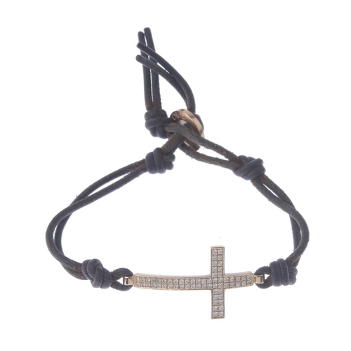 1265 - (546959-1-A) A diamond and leather bracelet. Designed as a brilliant-cut diamond cross, suspended fr...