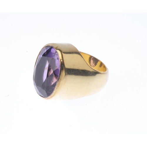 1267 - (546960-1-B) An amethyst single-stone ring. The oval-shape amethyst, with tapered shoulders and plai...
