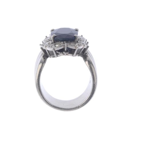1276 - (547034-2-A) A sapphire and diamond ring. The oval-shape sapphire, within a brilliant-cut diamond fo...