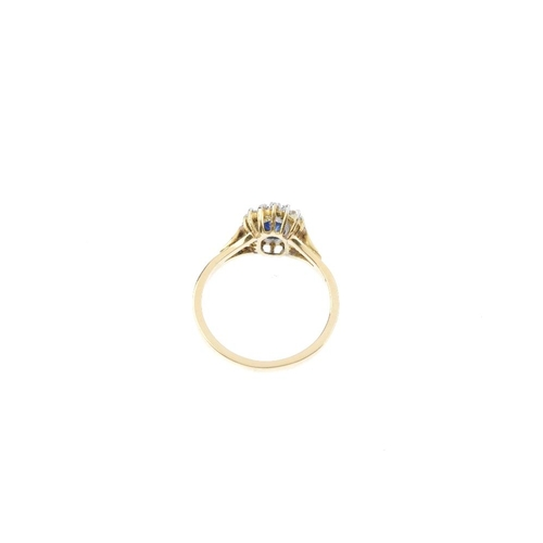 128 - An 18ct gold sapphire and diamond cluster ring. The oval-shape sapphire, within a single-cut diamond...
