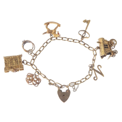 1286 - (547968-1-A) 9ct Gold Charm Bracelet. The curb link chain, suspending seven charms, to the heart-sha...